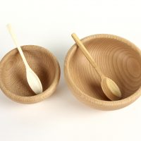 Two carved wooden bowls with a bone and a wooden spoon
