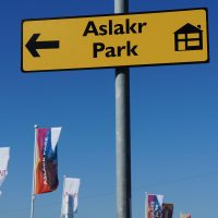Yellow new housing development sign for Aslakr Park