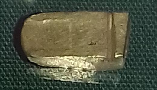 A rounded gold ingot terminal cut from an ingot of rectangular cross-section.