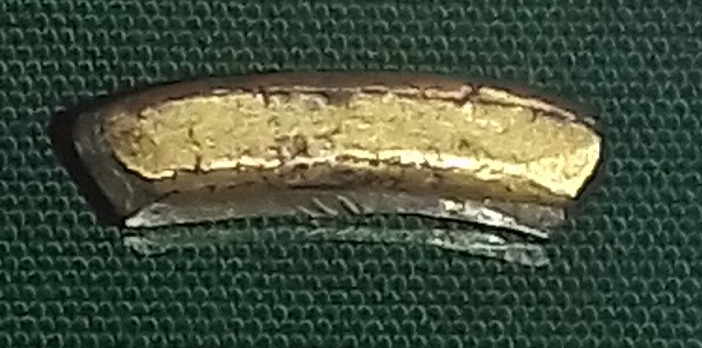 A curved section of gilt copper-alloy. It is square in cross-section and broken at both ends.